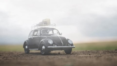 NITRA, SLOVAKIA - JUNE 28 2018: Volkswagen Beetle with suitcases on the roof. White clouds over Volkswagen Beetle. Classic car VW Beetle and white clouds.