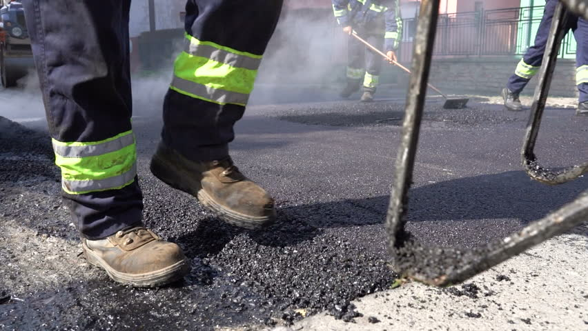 Constructions Workers Working on Road Construction - Slow Motion. Steam is Rising From The Hot Asphalt Surface. Worker Leveling Fresh Asphalt On A Road Construction Site. | Shutterstock HD Video #1026476243