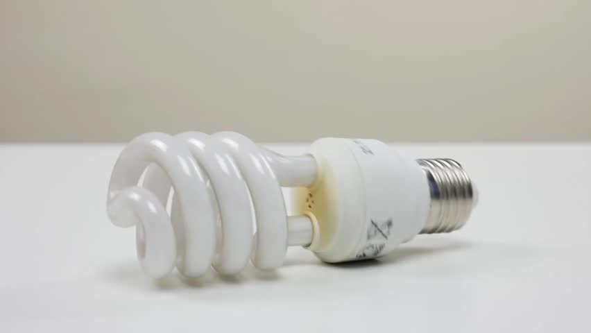 Energy saving light bulb rolling on white table | Shutterstock HD Video #1026508493