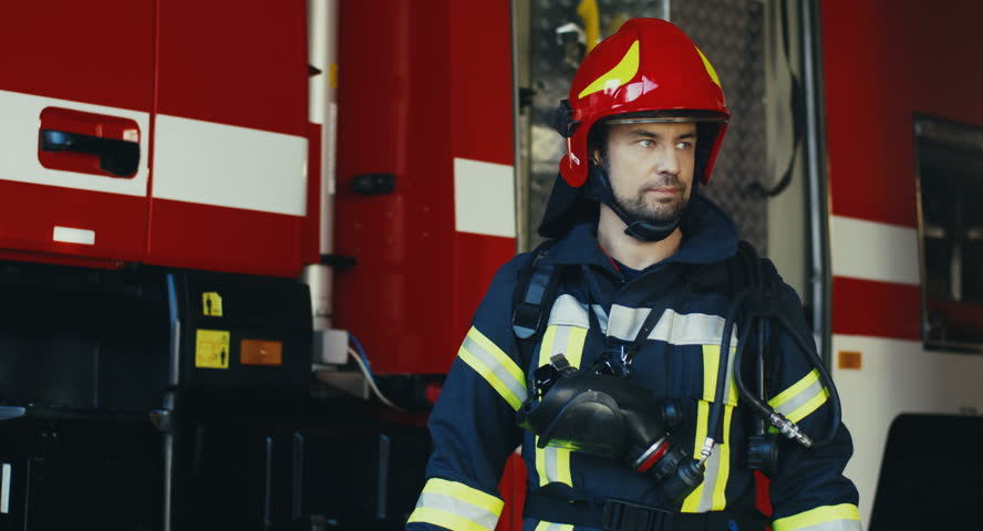 Portrait shot of the handsome Caucasian fireguard in the equipped costume and helmet looking at the side and then turning his head to the camera on the red fire truck background.