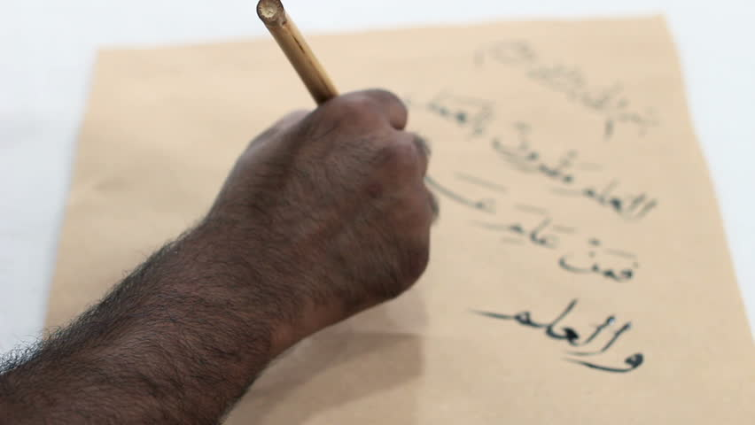 """Calligrapher writes Arabic words on an old paper. Translation: """"Knowledge should be accompanied with work, those who know must represent their knowledge by working"""" 