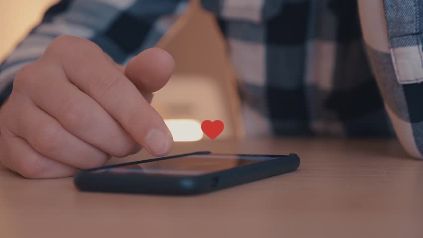 Close up of young man using smartphone with likes and loves icon floating out of smart phone   Shutterstock HD Video #1026571253