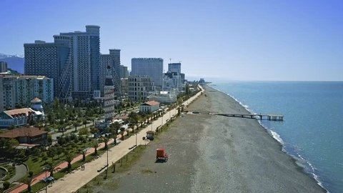 Batumi beach zone with a blue Black Sea water, stones, modern town appartments