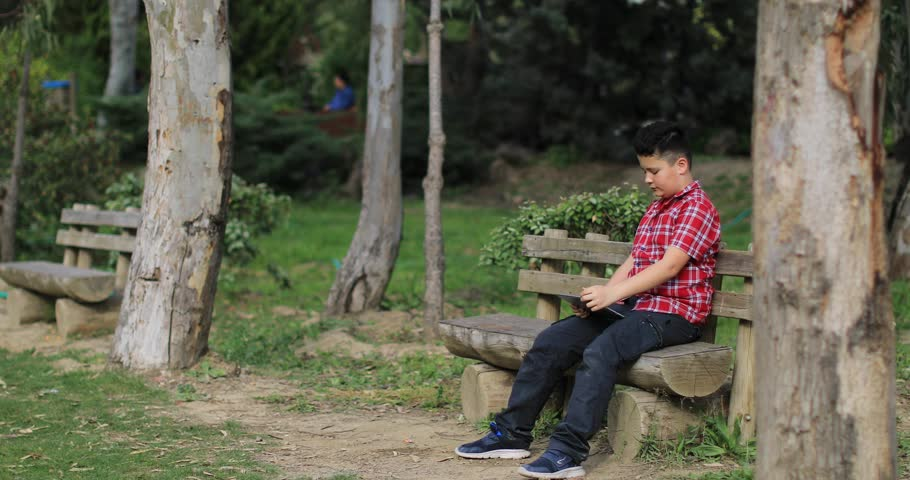 Portrait of a preteen boy with digital tablet computer sitting park bench at the outdoor. Kid watching to screen, reading, typing, playing games. Technology, internet communication and people conc