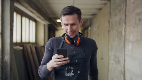 Medium shot of carpenter with protective earmuffs around his neck walking along corridor in industrial building and text messaging on cell phone in slow motion