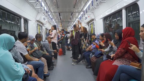 JAKARTA, Indonesia - March 26, 2019: Passengers using mobile phone in Mass Rapid Transit (MRT) subway train Jakarta. Shot in 4k resolution