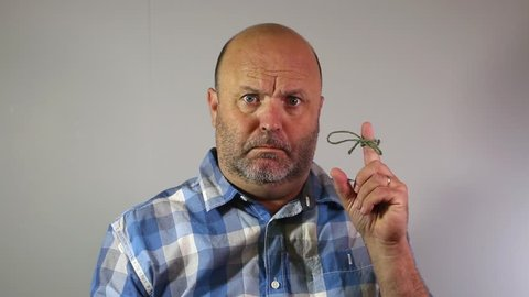 A man with a worried expression as he tries to remember why string is tied around his finger.