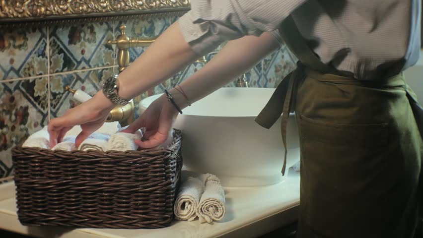 Woman cleaning lady puts clean white soft towels in basket on table with sink, hands close up