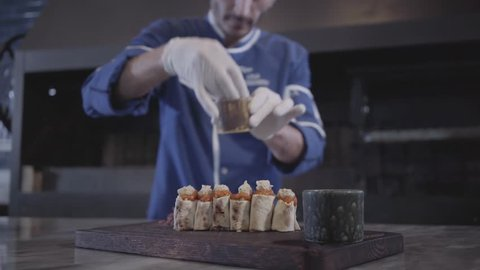 Professional cook cooking tasty kebab wrapped in lavash pita in modern restaurant close up. Turkish cuisine