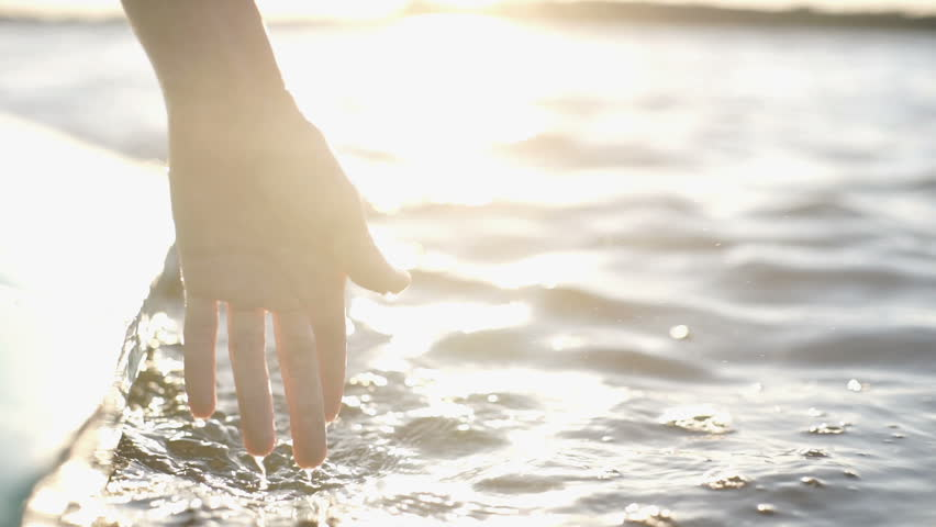 At sunset, close-up the hand of a girl moving through the water | Shutterstock HD Video #1026715013