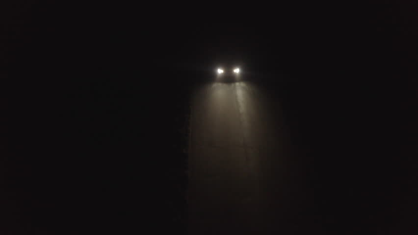 Aerial view tracking a car driving down a rural lane at night at speed.