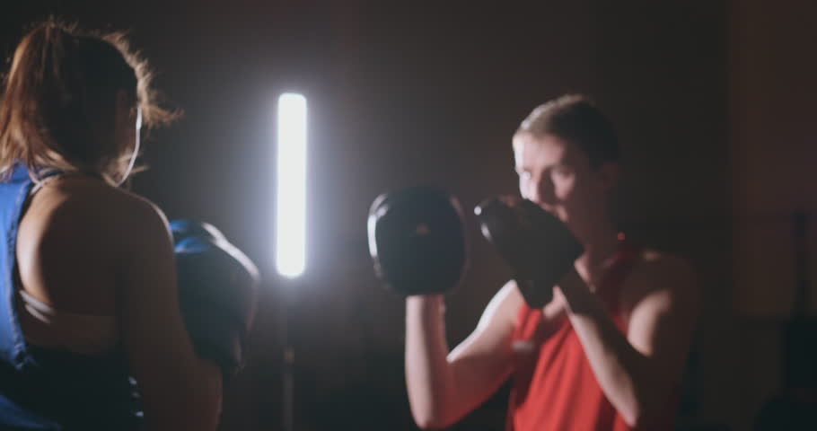 Medium shot of beautiful fitness woman boxer treneruemsya strike speed focus mitts with a coach in a Boxing club. slow motion | Shutterstock HD Video #1026766763