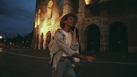 Overjoyed emotional female traveler walking near Coliseum and talking with friend on smartphone satisfied with exciting trip and good international connection in roaming. Excited hipster girl calling