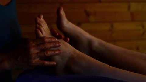 Reflexology foot massage treatment in tranquil zen environment, female massage therapist preforming reflexology on young woman at health spa retreat holiday, lady enjoying a pampering massage