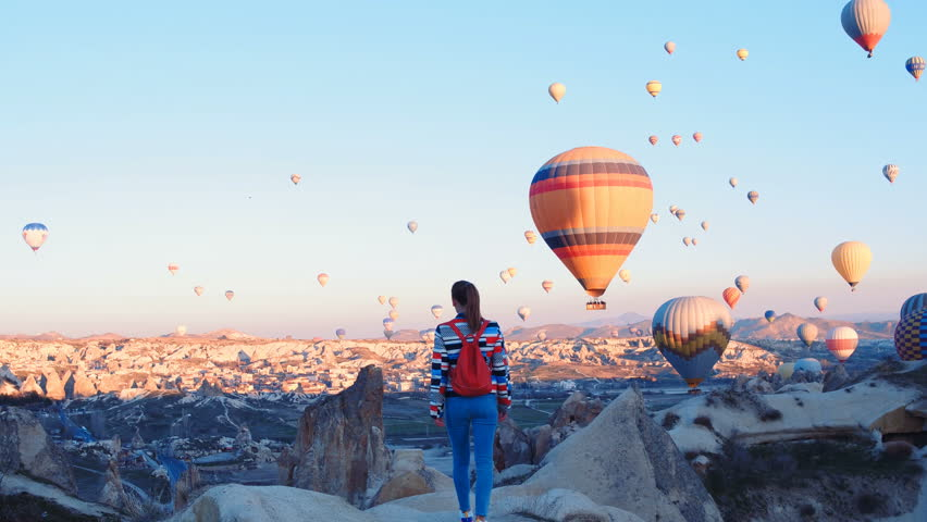 Yoing traveler with backpack looking to the air baloons. sporty girl and a lot of hot air balloons. The feeling of complete freedom, achievement, achievement, happiness | Shutterstock HD Video #1026792233