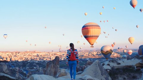 Yoing traveler with backpack looking to the air baloons. sporty girl and a lot of hot air balloons. The feeling of complete freedom, achievement, achievement, happiness