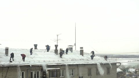 Many men throw white snow from the roof of a multi-storey building. Heavy seasonal male labor. People work as a shovel. They quickly clean the roof of excess snow. Slow motion
