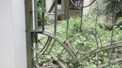 Slow Dolly in opening an old rusty metal gate to a backyard of an abandoned house.