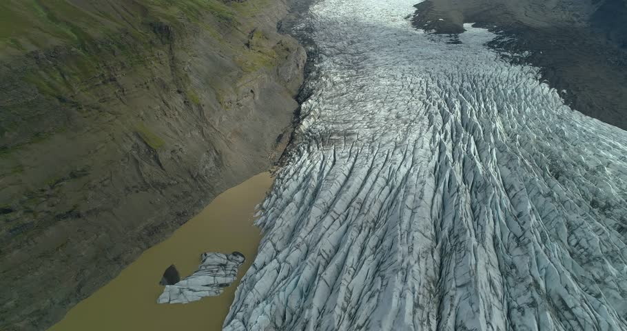 Drone shot looking down rising up over the end of a glacier toe next to a cliffy mountain in Iceland. Glacier lake to the left of the frame. | Shutterstock HD Video #1026868253