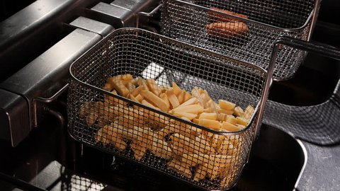 French fries start frying in a wire basket - being lowered in hot oil basin of a deep fry equipment, close up, camera approach, top view, slow motion