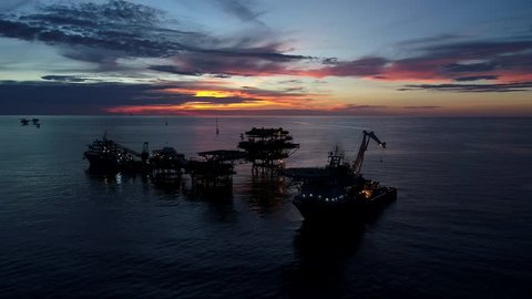 Silhouette of oil production platform or oil rig with supply vessel during sunset at oil field