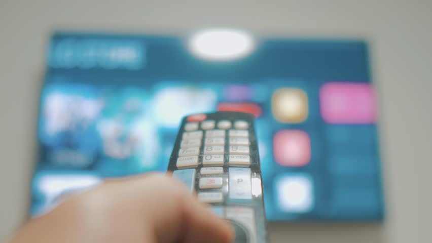 Smart tv with apps and hand. Male hand holding the remote control turn off smart tv. man hand controls TV lifestyle holding remote. concept internet online cinema | Shutterstock HD Video #1026901823