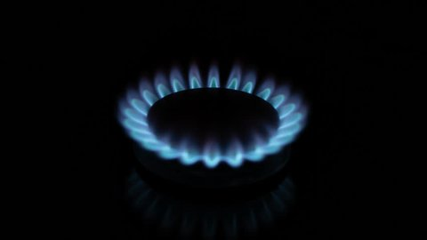 Close up Timelapse  central shot of natural gas inflammation in stove burner. Gaz fire burns, house gas flames on black background. Blue gas fire shot in darkness