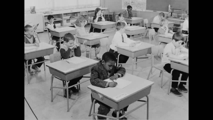 CIRCA 1960s - A teacher reads sentences and students circle words in their workbooks in a classroom in an elementary school.