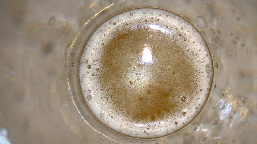 Glass of beer with bubbles top view. Beer foam bubbles closeup   Shutterstock HD Video #1026963503