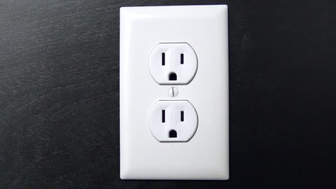 Male hand plugs in and unplugs a two pronged cord into the bottom outlet of an American electrical socket, centered close up