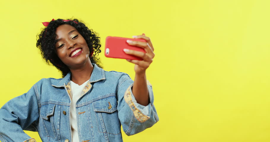 Young charming African American woman smiling, posing and blowing kisses to the smartphone camera while standing on the yellow background and taking selfie photos.