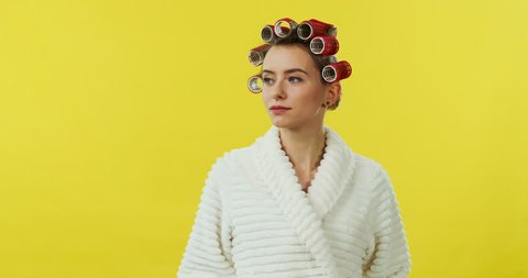Portrait of the young pretty woman in the white bathrobe and curlers turning her head to the camera and smiling cheerfully on the yellow background.