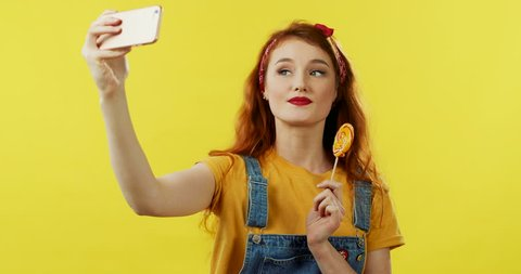 Cute Caucasian red-haired young girl taking selfie photo on the smartphone camera and posing with a lollipop on the yellow background.