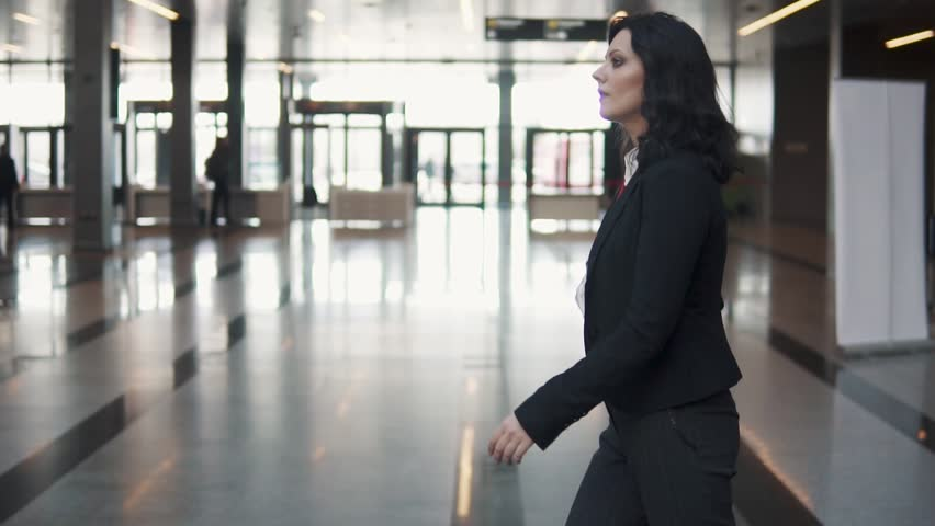 A young woman in a business suit walks through the lobby of a modern office building. | Shutterstock HD Video #1027083083