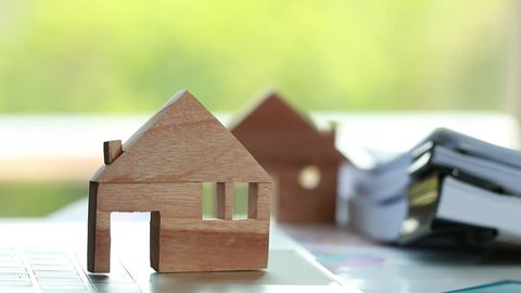 Property home model for loan real estate to buy new for family or mortgage investment concept: Wooden house models on laptop computer with chart report documents contact customer for wealth management