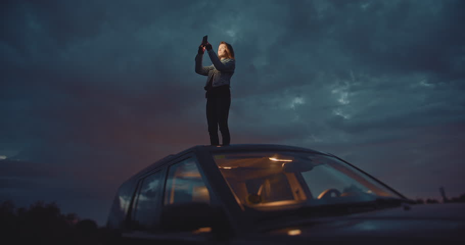 Slow Down To Enjoy Your Trip, Traveler woman takes pictures at night on smartphone device while standing on the roof of the car, Connection in Mountains,  #1027149923
