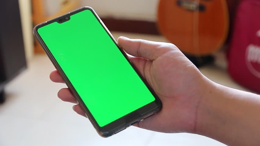 Crop shot of man's hand using smartphone with green screen in his home touch screen tapping sliding searching application message | Shutterstock HD Video #1027153373