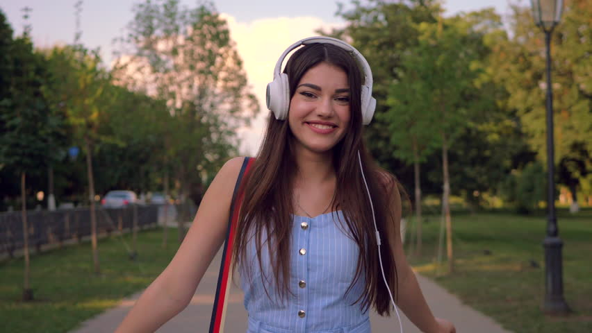 Enchanting lady is walking outdoors in park in summertime, listening to music in her headphones. Stylish woman is wearing blue romper suite.  | Shutterstock HD Video #1027157513