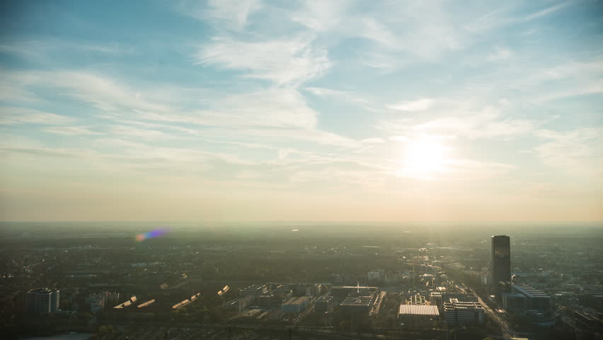 Timelapse of the munich skyline from above with light trails from traffic during sunset