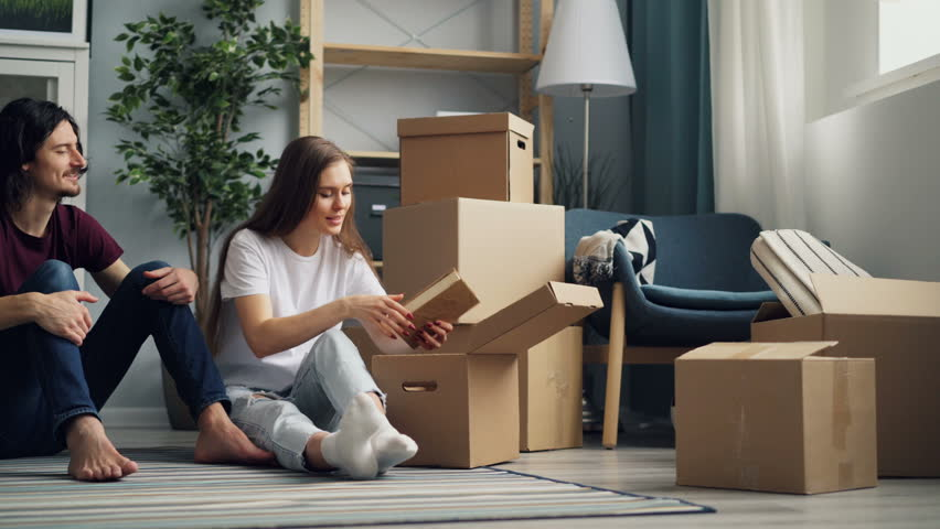 Young man and woman are unpacking after moving in together taking things from box looking at them and talking. Relocation, relationship and flat concept. | Shutterstock HD Video #1027227113