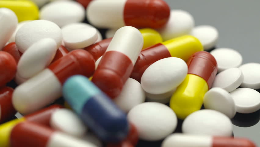 Colorful pills with capsules and tablets on white table #1027245383