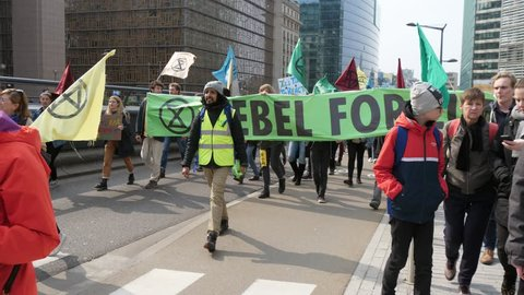 Brussels, Belgium - March 30, 2019:Energetic view of a group of green peace people walking, chanting and keeping a banner Rebel for Life in a sunny street in Belgium