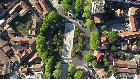Circular movement vertical aerial view over a roundabout with trees in Nîmes France sunny day
