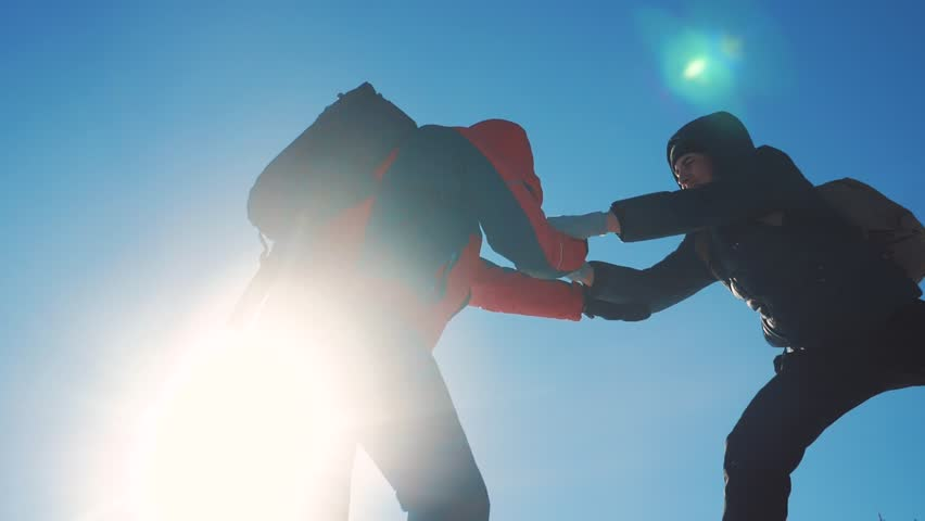 teamwork tourists winter snow business travel trip lends a helping hand. two men with backpacks hiking help each other silhouette in mountains with sunlight lifestyle . slow motion video. rock