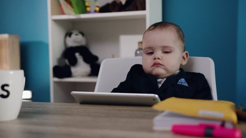 close up view of lovely toddler boy in business suit with extremely cute cheeks sits at the table with tablet by the baby boss?s mug. Successful baby, childhood happiness, little wonder. Child?s