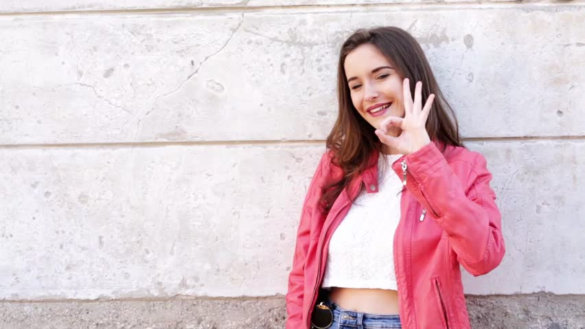Surprised girl winks at the camera, makes ok sign . Young adult making gestures and smiling. | Shutterstock HD Video #1027407953