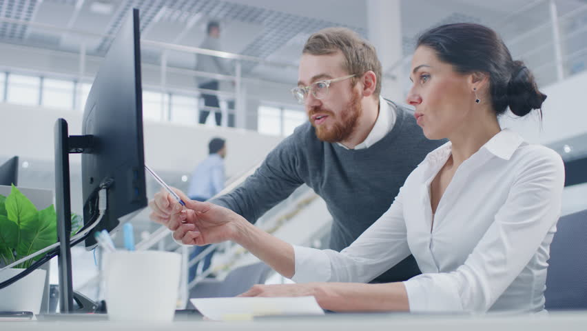 Beautiful Businesswoman Uses Desktop Computer, Consults Her Project Manager about Documents with Graphs and Statistics. In the Background Big Corporate Firm Office | Shutterstock HD Video #1027449083