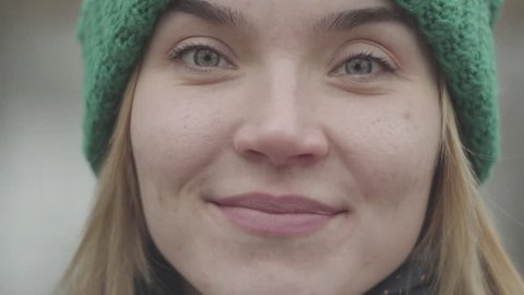 Close up portrait of confident cute young woman in green hat and yellow coat drinking tea or coffee from the thermos in the park looking in camera close up. Positive lady rests outdoors.