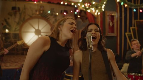 Panning shot of women singing duet in band rehearsing in nightclub / Provo, Utah, United States