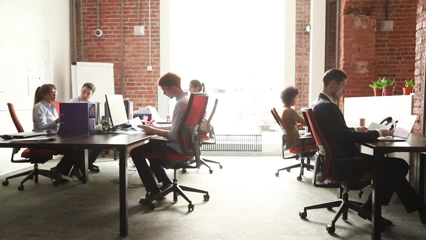 Business people office workers group using pc working talking in big modern coworking space, employees team women men sitting at desks with computers in modern enterprise interior at workplace | Shutterstock HD Video #1027488413